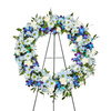 Blue Remembrance Wreath holds White Carnations, Dendrobium Orchids and Blue Daisies