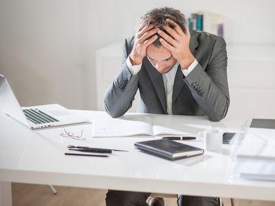 איש בשולחן משרדי מחזיק את הראש