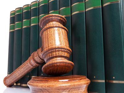פטיש בית משפט על רקע ספרים ירוקים