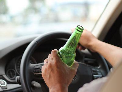 נהיגה בשכרות אדם מחזיק בקבוק תוך כדי נסיעה