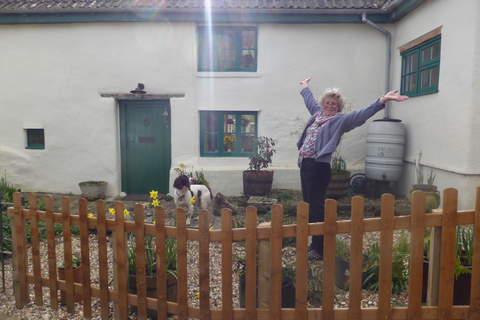 Image-of-a-happy-customer-Nikki-standing-by-the-discreet-high-quality-below-ground-WPL-Diamond-package-wastewater-sewage-treatment-pant-for-off-mains-drainage- at-a-beautiful-cottage-in-the-uk-the-wpl-diamond-replaced-a-leaking-septic-tank.