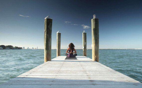 mujer haciendo yoga en el muelle por agua