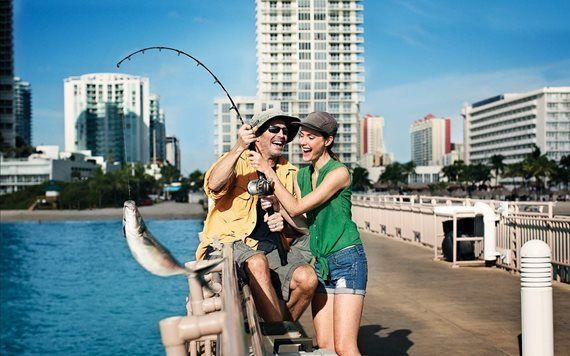 couple holding up fish on pier