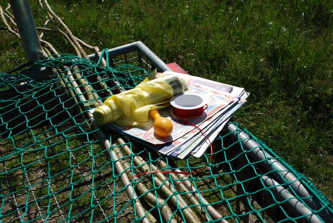 Die Äste werden am Tag vor der Wiesenmahd mit Gegenständen wie Kunststofftüten, Lappen, Schleifen oder Zeitung präpariert. Alles sollte sich im Wind gut bewegen können.