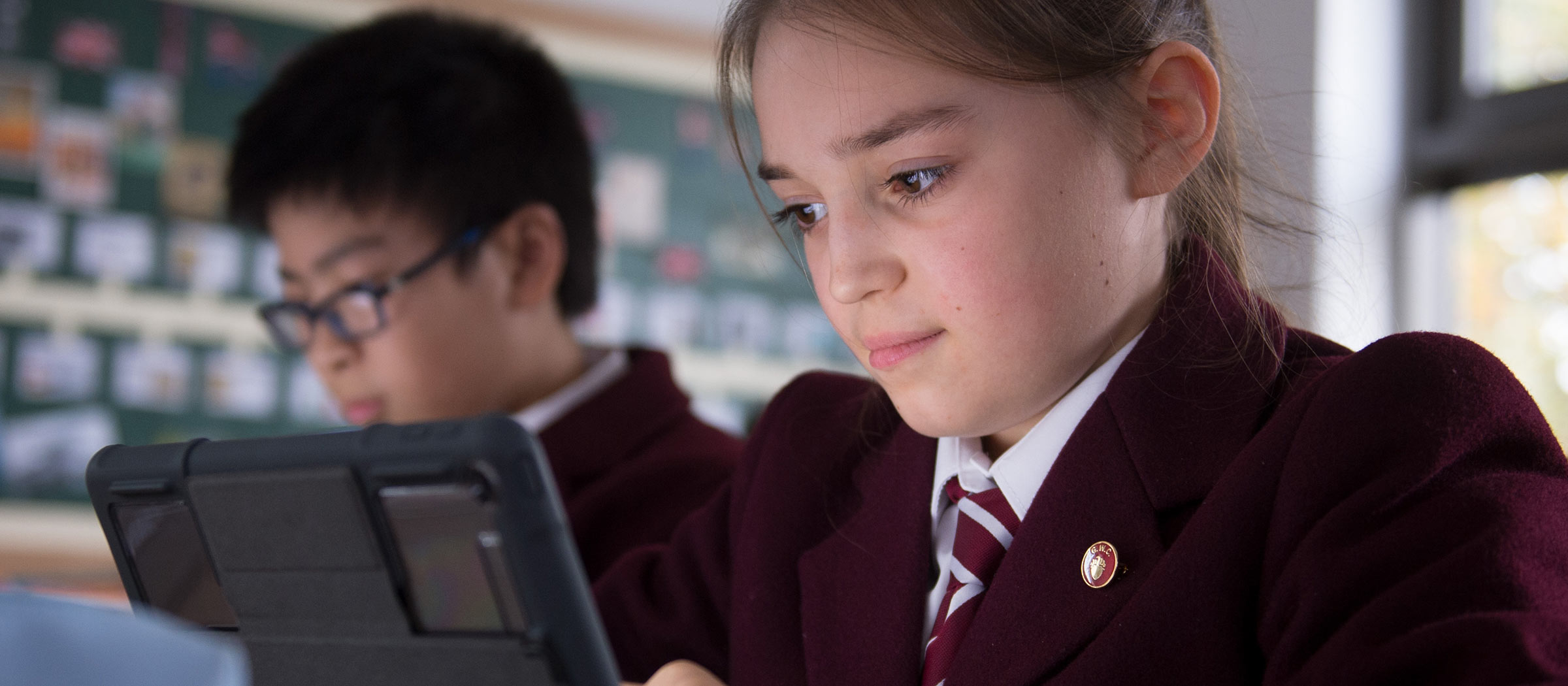 Girl and boy looking at screens in a classroom