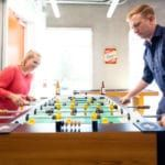 photo of two people playing foosball in HS building