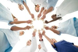 Doctors and nurses standing together in a circle holding puzzle pieces out