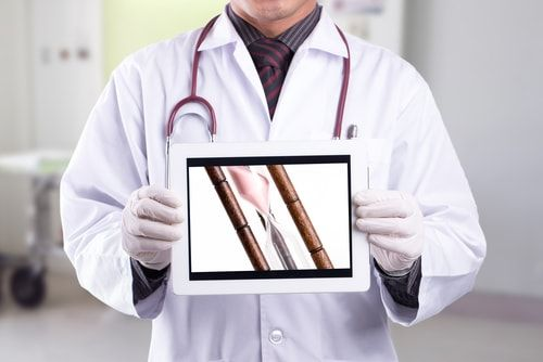 doctor holding iPad type device showing hour glass