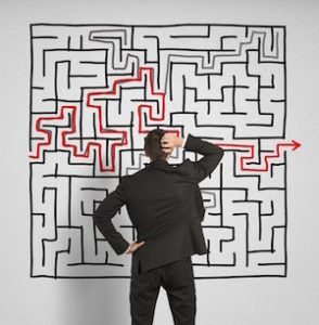 Man in suit looking at large wall maze in confusion
