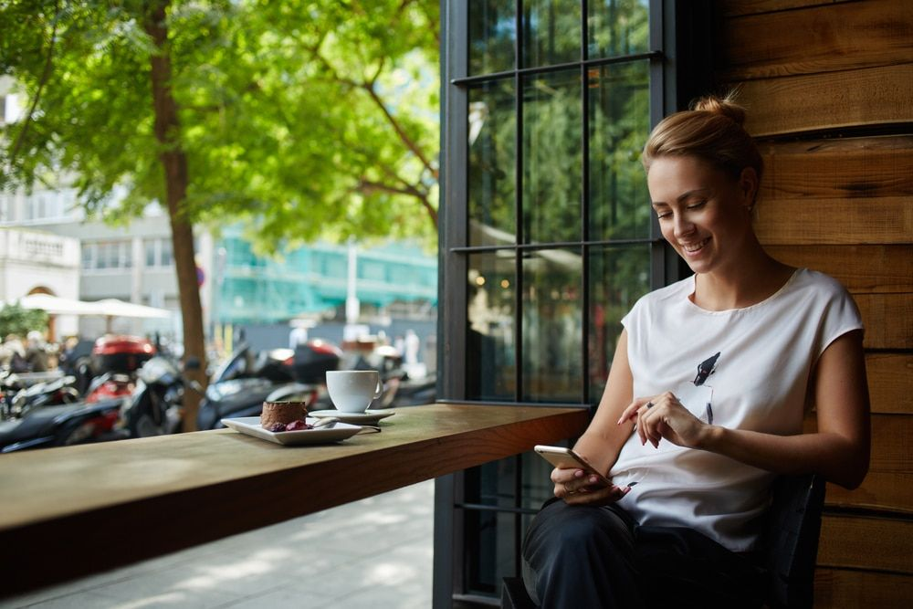 woman having coffee while on iPhone