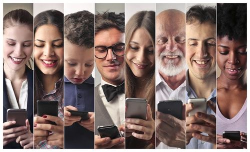 photo of multiple people looking at phone
