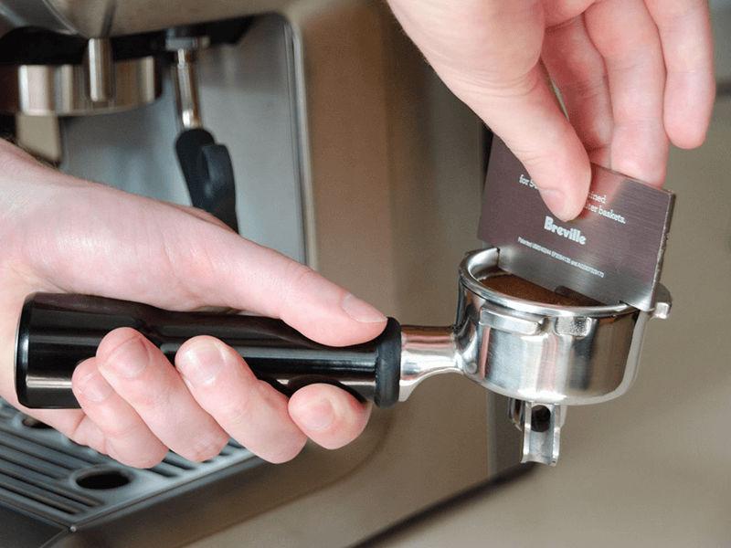 Dùng dao Razor để gạt cafe hoặc định lượng lại mức cafe