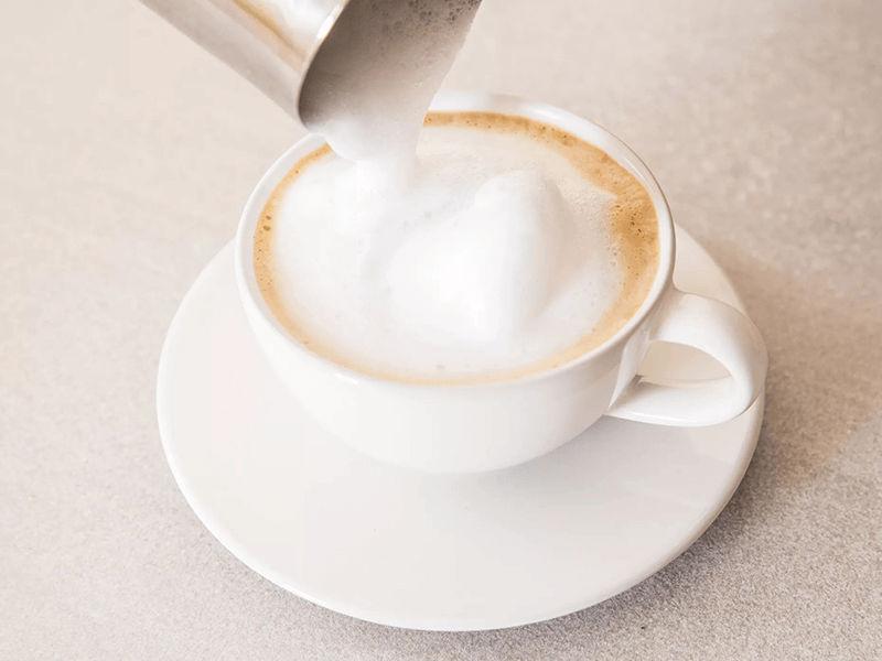 Hãy rót sữa vừa được đánh lên trên bề mặt espresso