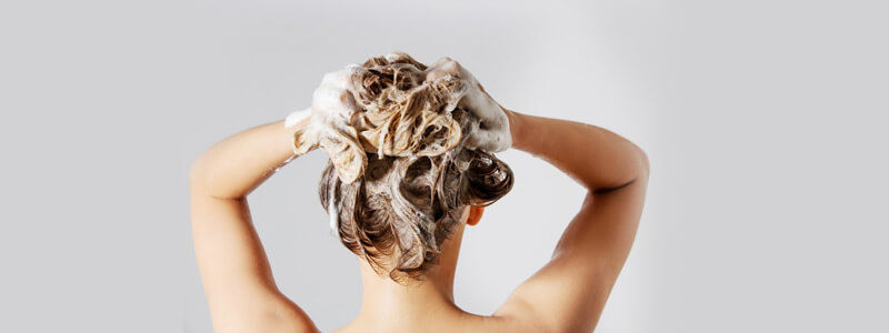 Woman using shampoo on hair