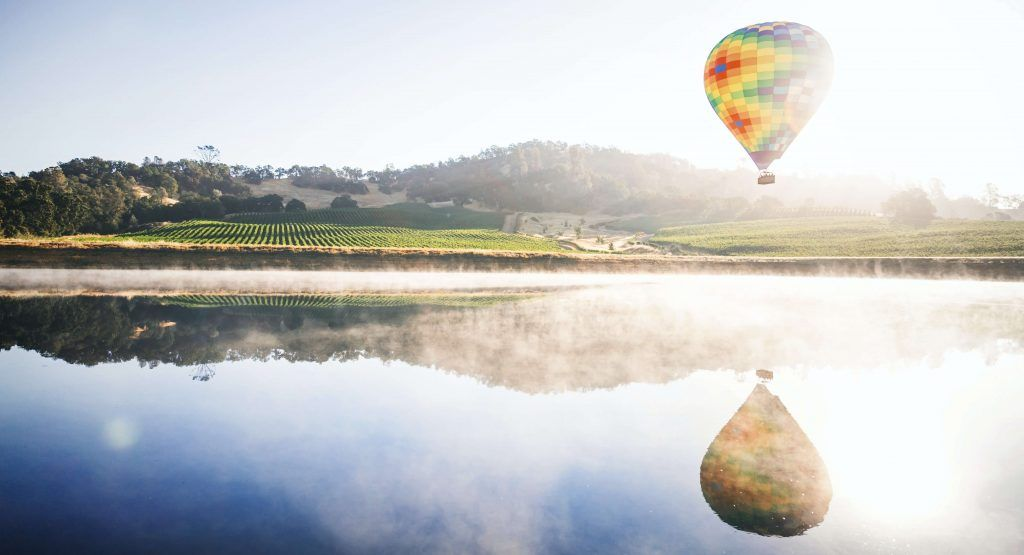 Hot air balloon over Napa Valley vineyard sunrise