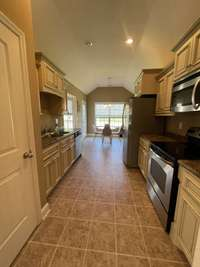 Galley kitchen with custom cabinets and stainless steel appliances with eat in breakfast nook view 4