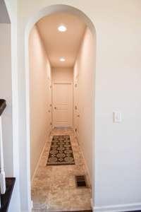 Hallway to large understair storage, utility room, and garage