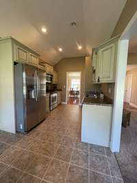 Galley kitchen with custom cabinets and stainless steel appliances view 3