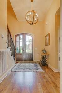 View looking back towards the front doors and foyer.  Beautiful light fixtures throughout the home