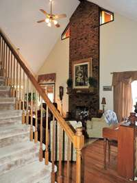 Spacious living area with floor to ceiling fireplace, vaulted ceiling and beautiful hardwood floors.