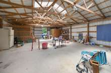 The massive 30x50 shop has electric, large entry for vehicles and covered lean-to