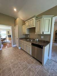 Galley kitchen with custom cabinets and stainless steel appliances view 2