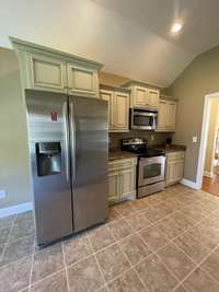Galley kitchen with custom cabinets and stainless steel appliances