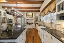 Luxury countertops, beautiful farmhouse sink, double drawer dishwasher, handmade tile backsplash with warm rich hickory floors to accent this one of a kind kitchen