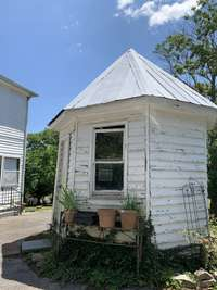 Separate outdoor storage shed sits a well that has since been covered.