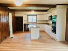 Kitchen open to family Room with dutchlap wood walls and access to Formal Dining Room