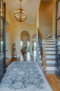 Foyer looking upstairs.  Staircase with hardwood and wrought iron spindles
