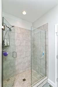 Large walk in glass shower in your owner suite with custom tile work.