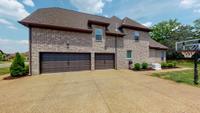 Large 3 car garage w/ oversize aggregate driveway