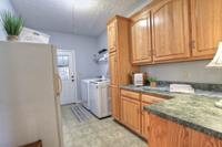 Plenty of room to store and fold clothes in this spacious laundry room that also leads down into sun room.