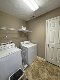 Utility room with additional storage closet.