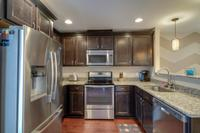 Granite counters and stainless steel appliances. Refrigerator even stays.