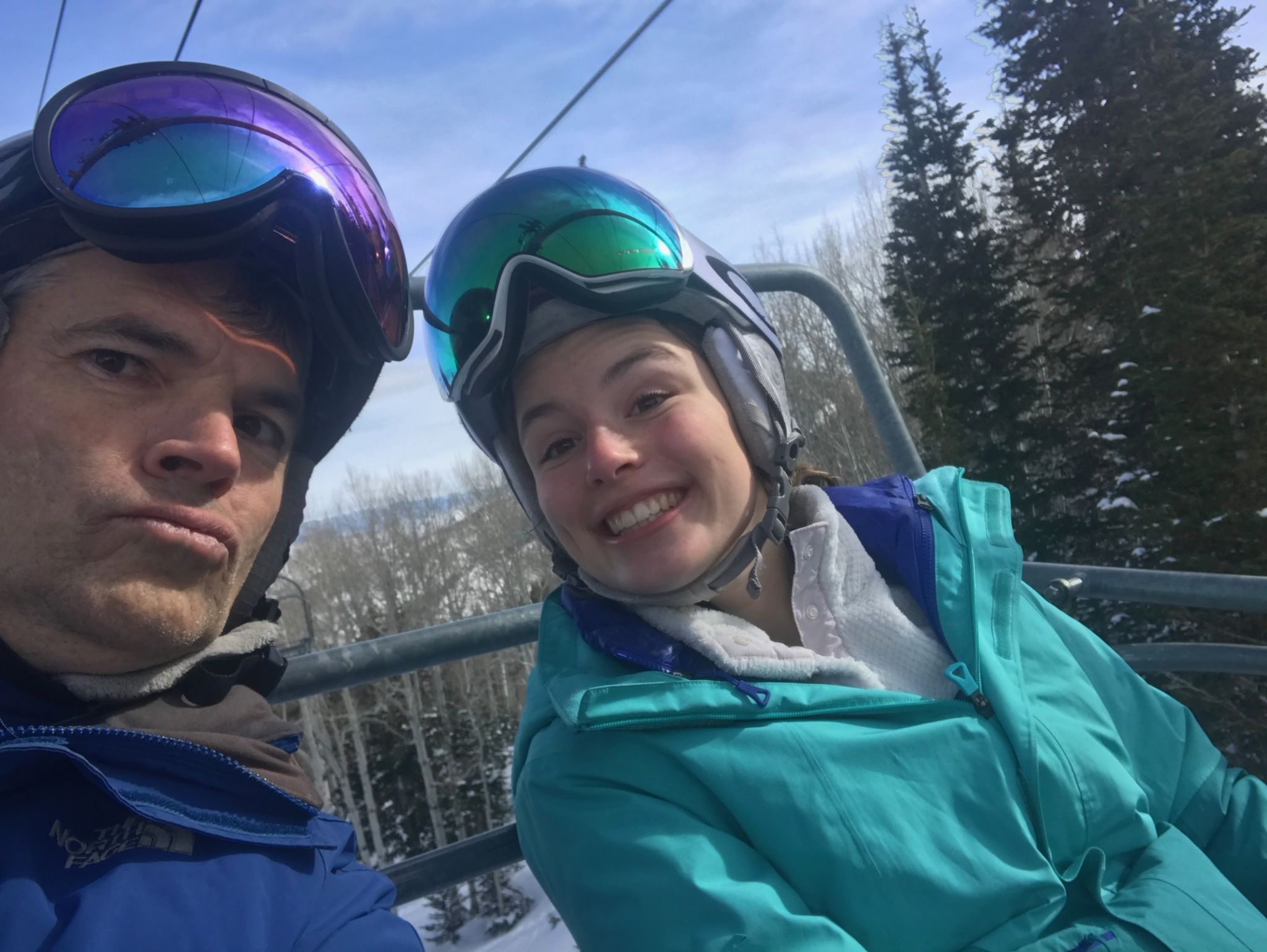 Alex Peters sitting with friend on a ski lift