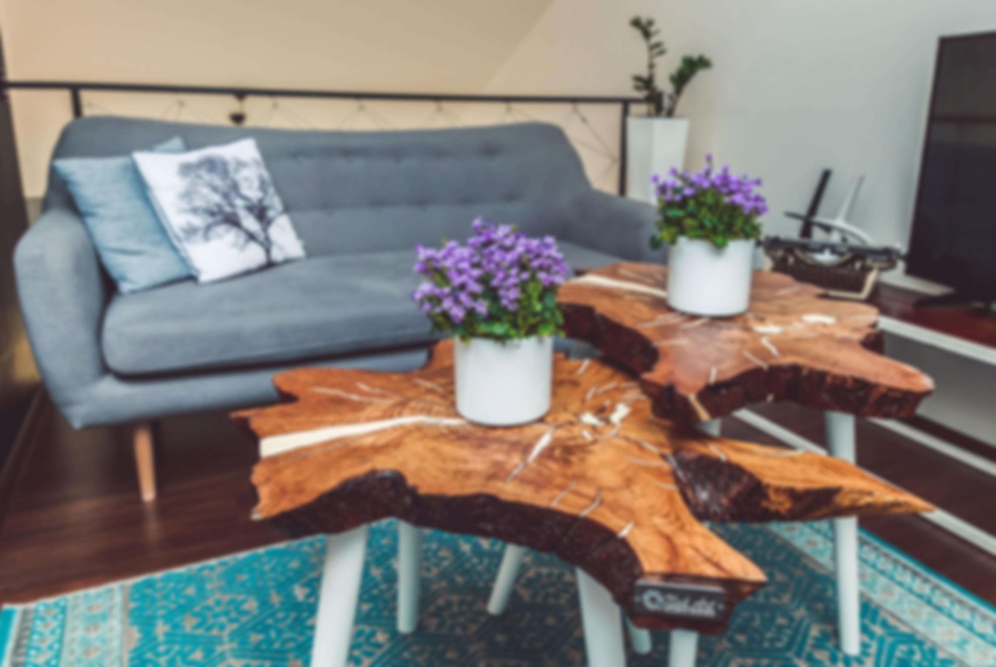 Zdjęcie z dwoma drewnianymi stolikami i szarą kanapą.