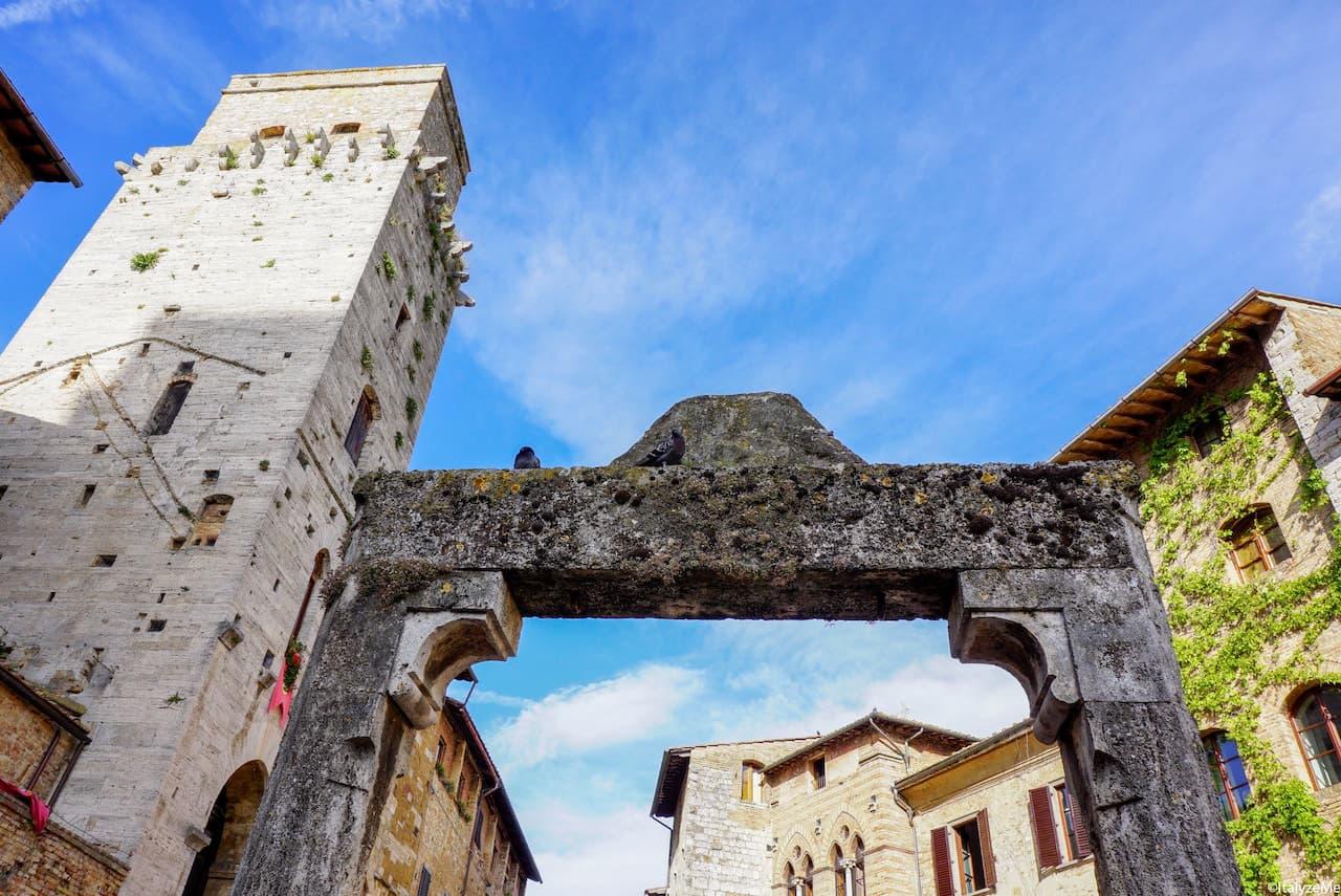 Pozzo di Piazza della Cisterna con l'imponente mole della Torre del Diavolo