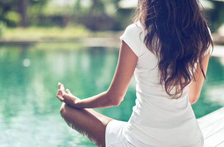 woman sitting in yoga pose by water