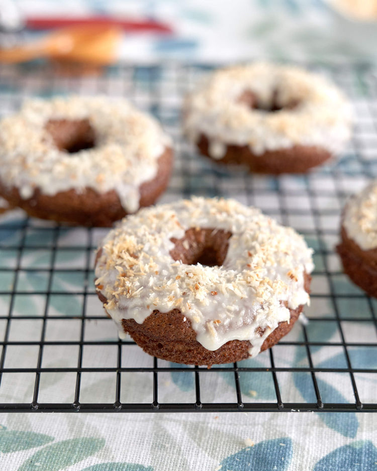 Gluten-free donut with coconut icing on a cooling rack.