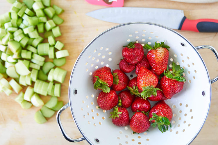 Strawberries in a collander and chopped rhubarb.