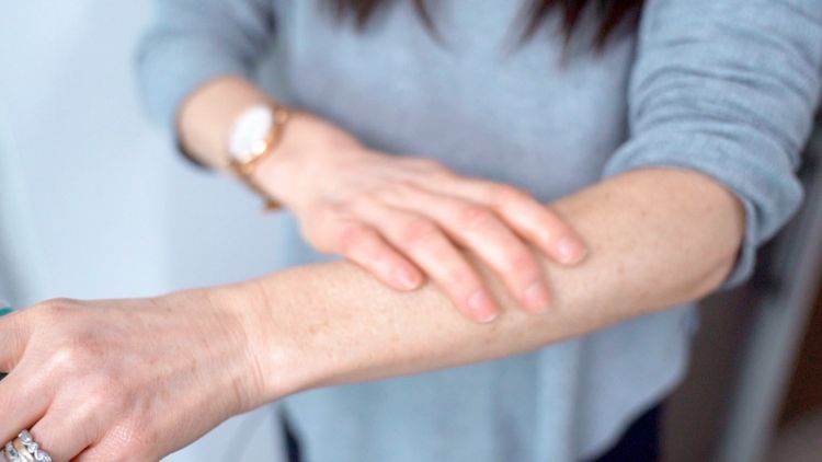 Rubbing body butter on arm