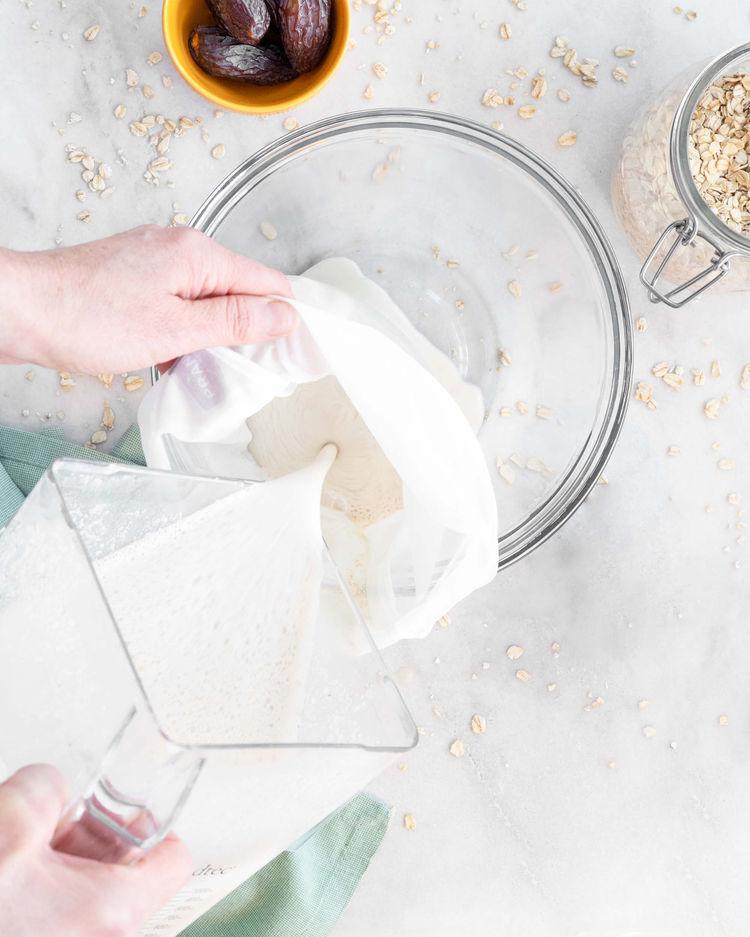 Oat milk being poured through strainer.
