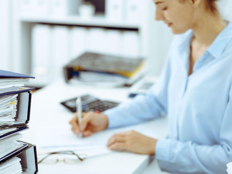 kobieta za biurkiem wystawia zaswiadczenia o zatrudnieniu