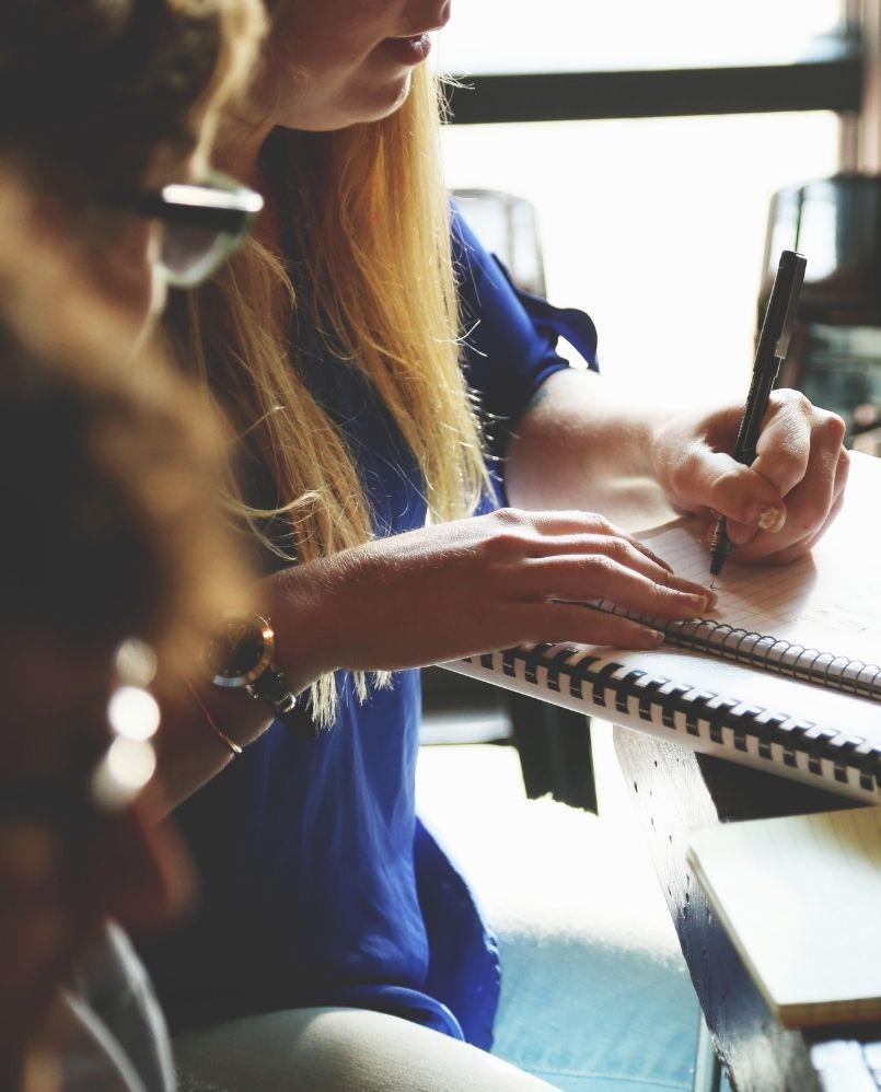 kobieta zapisuje pomysły na projekt do notatnika