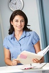Female doctor smiles while consulting medical records