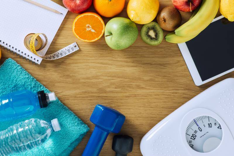 Fruits, weights, water bottles and scales for weight loss