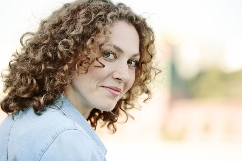 Happy curly haired lady looks into camera over shoulder