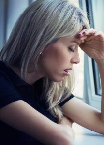 Stressed blonde woman by the window